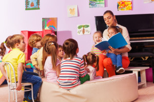 Large group of kids sit and listen to teacher reading a book and telling stories